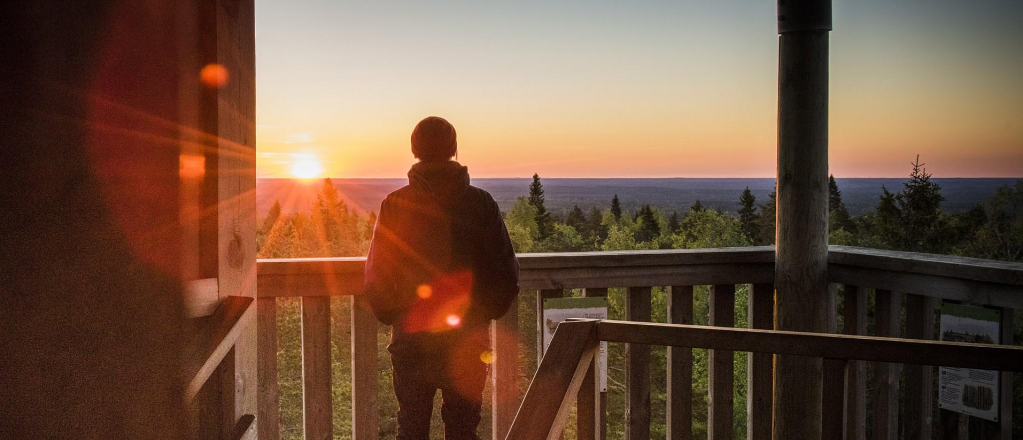Nainen Lauhanvuoren tornissa kesäyönä, aurinko horisontissa.