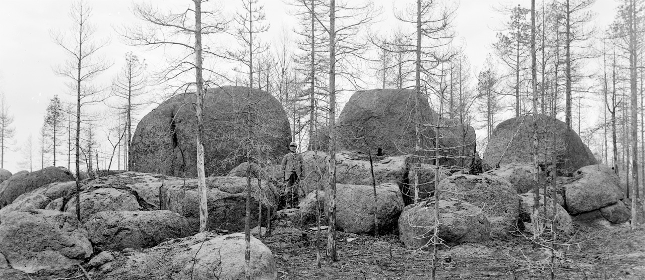 A man stands in between large rocks in 1890's